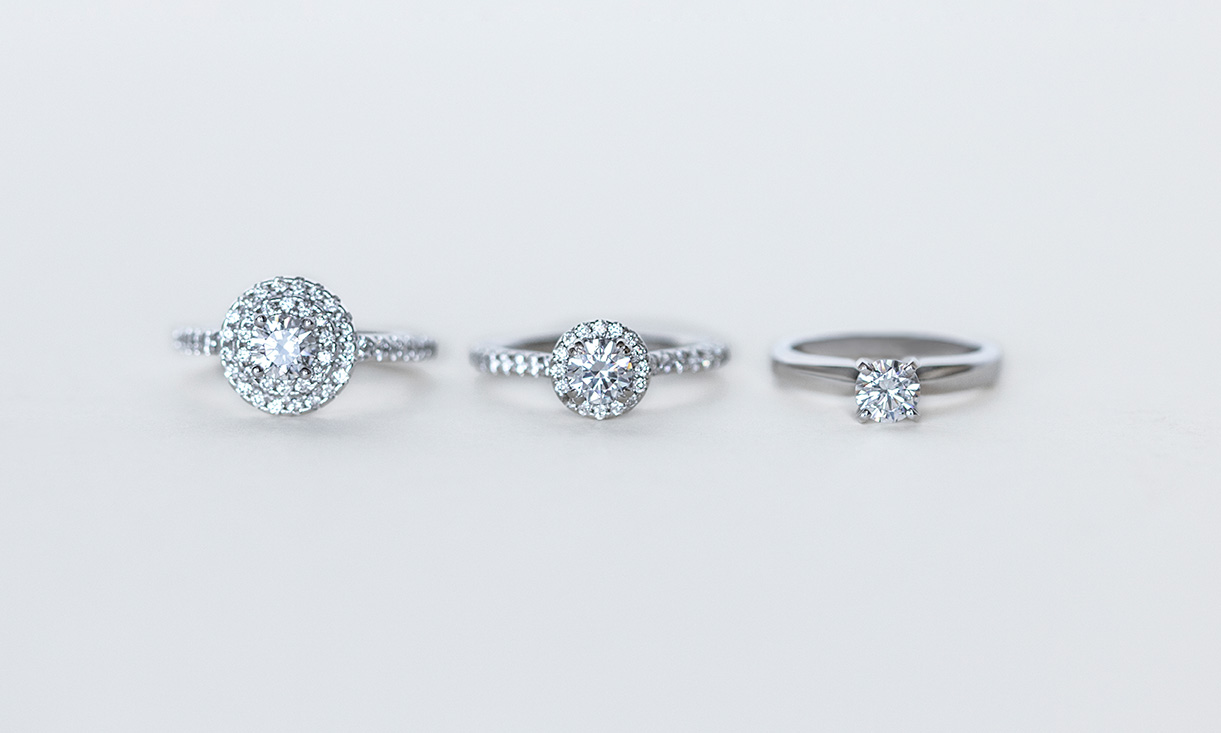 One double halo engagement ring, one halo engagement ring and a solitaire engagement ring.