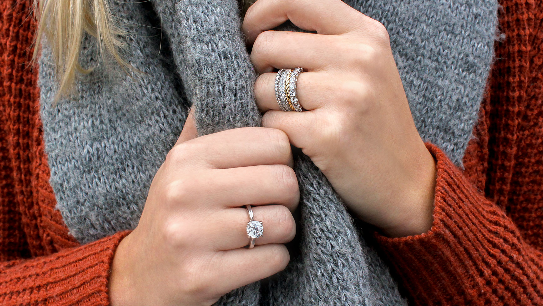 A women wearing a Diamond Nexus engagement ring on one hand and a mixed-metal band stack on her other.