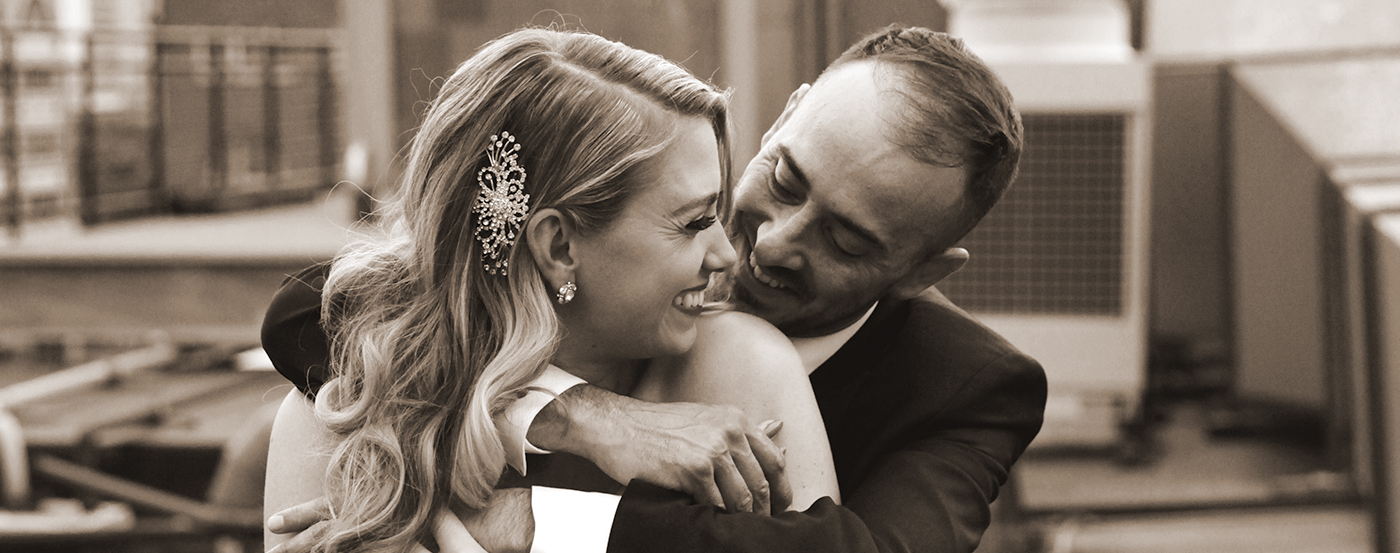 A bride wearing a dazzling barrette in her hair and being embraced by her husband.