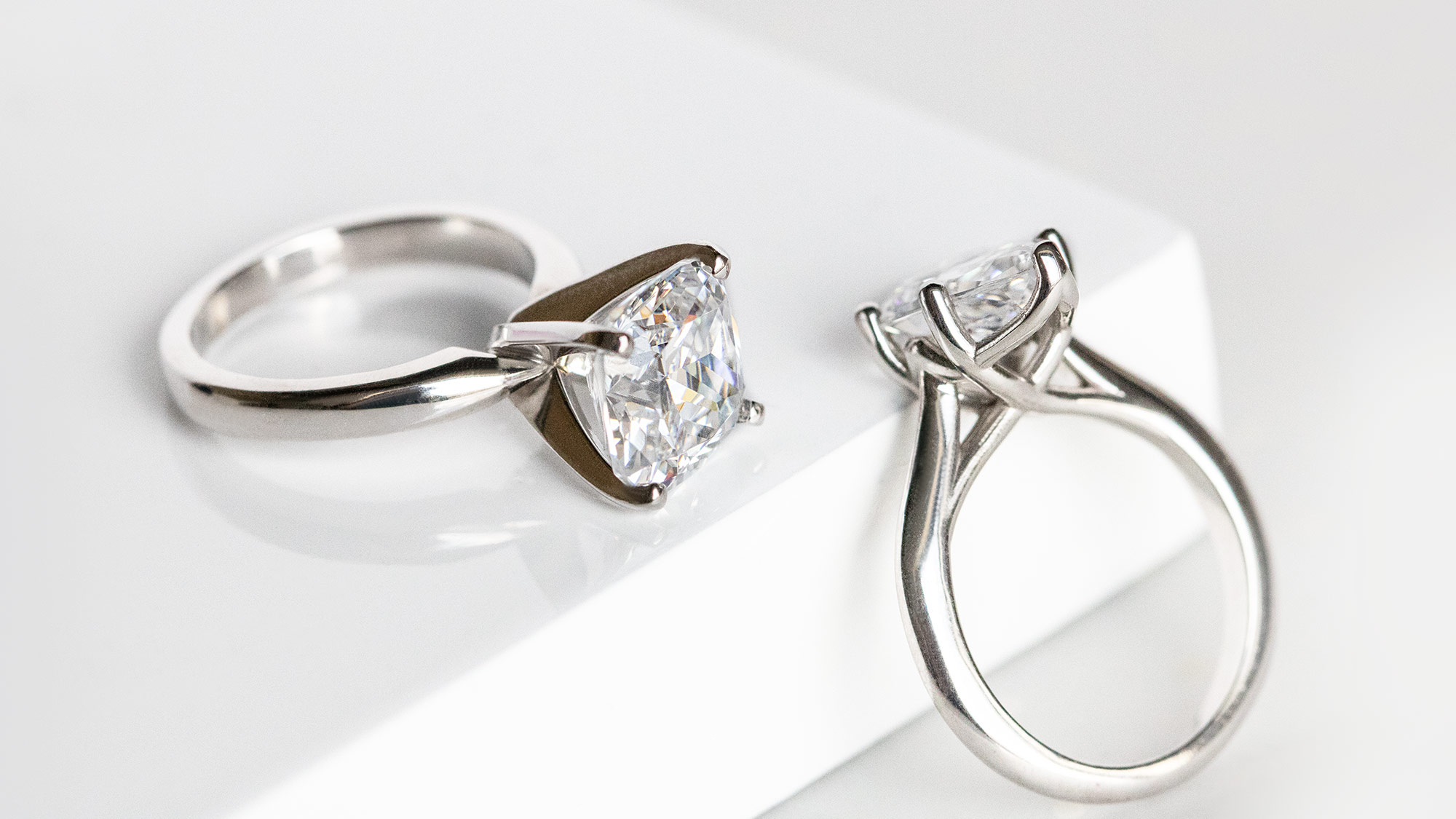 Two white gold solitaire Diamond Nexus engagement rings.