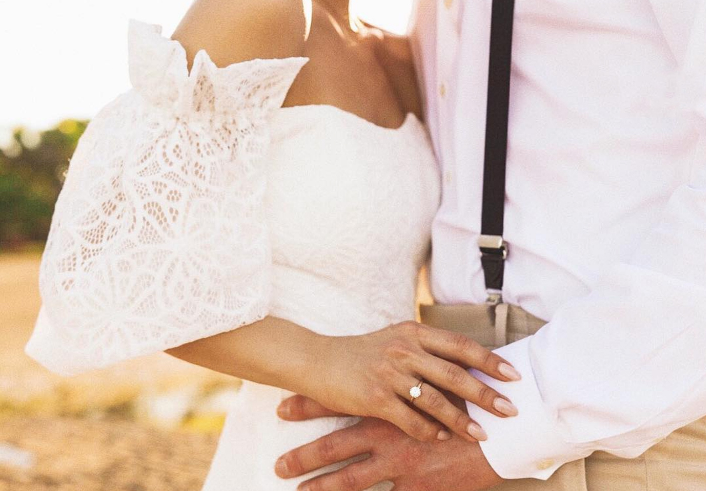 Newlyweds on their wedding day featuring a solitaire Round Brilliant cut engagement ring on the bride.