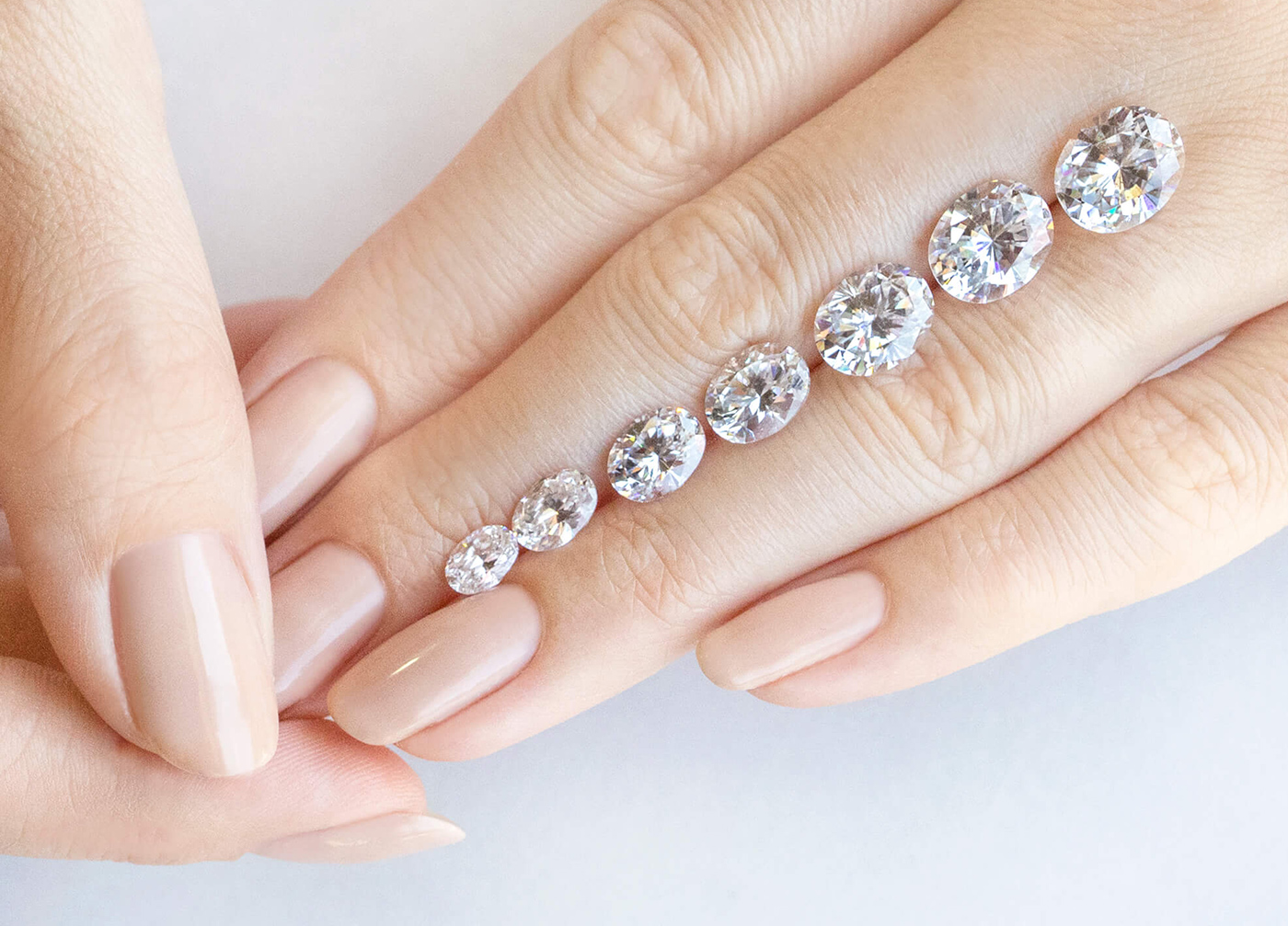 Loose Oval cut Nexus Diamond alternatives featured in varying carat weights resting on a hand.